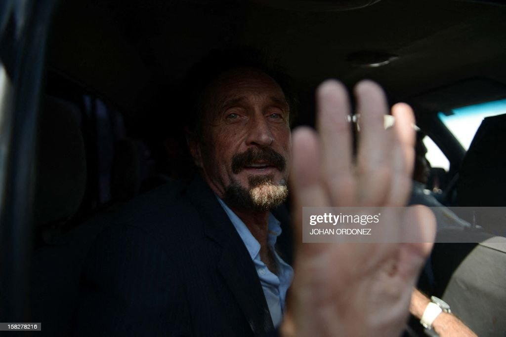 US anti-virus software pioneer John McAfee gestures as he arrives at the Aurora international airport in Guatemala City on December 12, 2012. McAfee escaped immediate deportation to Belize on Wednesday as Guatemala decided to expel the American back to the United States instead. McAfee, who entered Guatemala illegally after more than three weeks on the run, is wanted in Belize for questioning over his neighbor's murder last month.