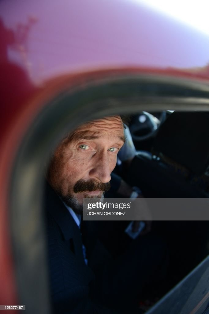 US anti-virus software pioneer John McAfee is transferred in a migration's car of Migration to the Aurora international airport in Guatemala City on December 12, 2012. McAfee escaped immediate deportation to Belize on Wednesday as Guatemala decided to expel the American back to the United States instead. McAfee, who entered Guatemala illegally after more than three weeks on the run, is wanted in Belize for questioning over his neighbor's murder last month. AFP PHOTO/JOHAN ORDONEZ