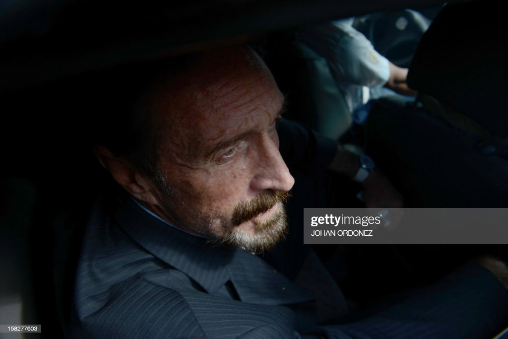 US anti-virus software pioneer John McAfee is transferred in a migration's car to the Aurora international airport in Guatemala City on December 12, 2012. McAfee escaped immediate deportation to Belize on Wednesday as Guatemala decided to expel the American back to the United States instead. McAfee, who entered Guatemala illegally after more than three weeks on the run, is wanted in Belize for questioning over his neighbor's murder last month.