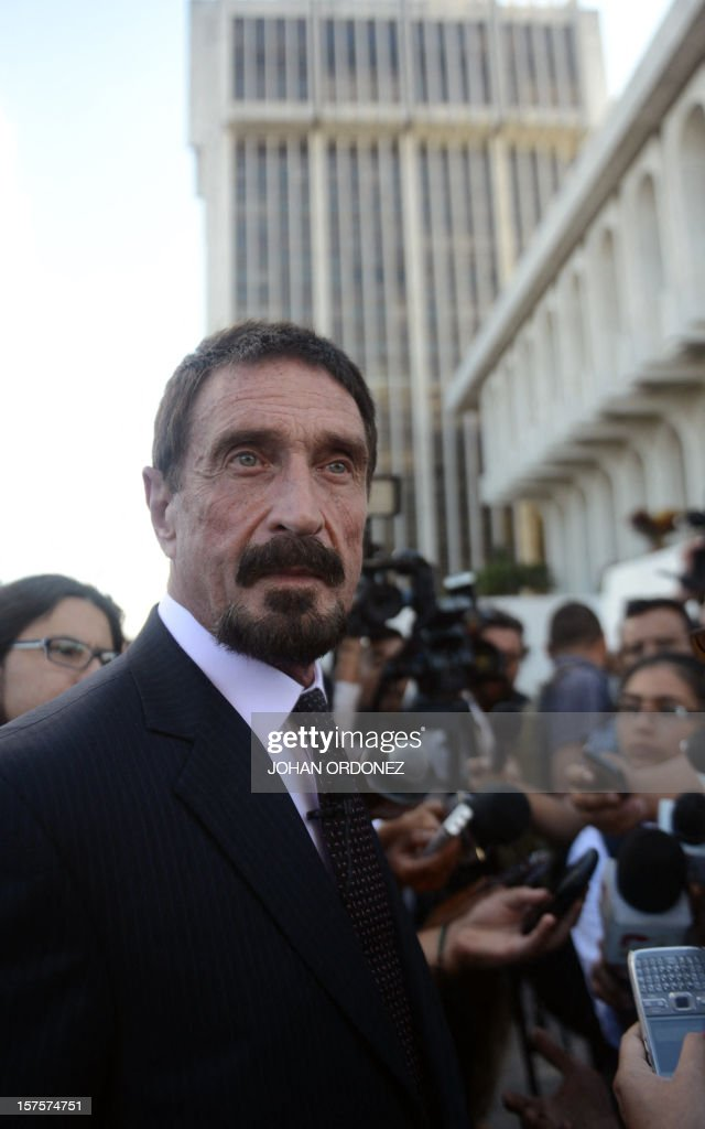 US anti-virus software pioneer John McAfee (L) listens to questions from a journalist in front of the Supreme Court in Guatemala City on December 04, 2012. McAfee, wanted for questioning over the murder of his neighbor last month in Belize, is seeking political asylum in Guatemala. AFP PHOTO / Johan ORDONEZ