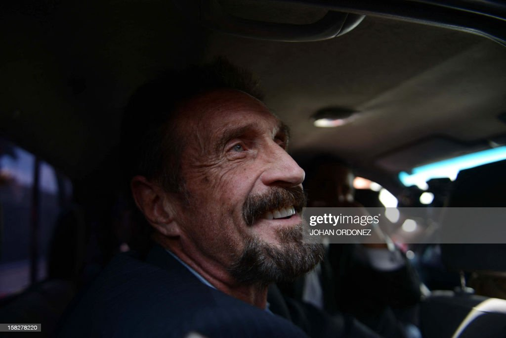 US anti-virus software pioneer John McAfee smiles as he arrives at the Aurora international airport in Guatemala City on December 12, 2012. McAfee escaped immediate deportation to Belize on Wednesday as Guatemala decided to expel the American back to the United States instead. McAfee, who entered Guatemala illegally after more than three weeks on the run, is wanted in Belize for questioning over his neighbor's murder last month.