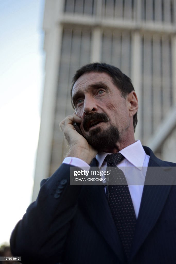 US anti-virus software pioneer <a gi-track='captionPersonalityLinkClicked' href=/galleries/search?phrase=John+McAfee&family=editorial&specificpeople=1353446 ng-click='$event.stopPropagation()'>John McAfee</a> speaks on his mobile phone in front of the Supreme Court in Guatemala City on December 04, 2012. McAfee, wanted for questioning over the murder of his neighbor last month in Belize, is seeking political asylum in Guatemala. AFP PHOTO / Johan ORDONEZ