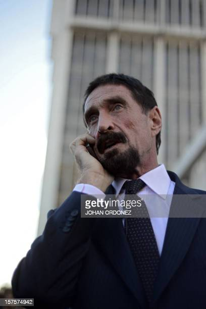 US antivirus software pioneer John McAfee speaks on his mobile phone in front of the Supreme Court in Guatemala City on December 04 2012 McAfee...