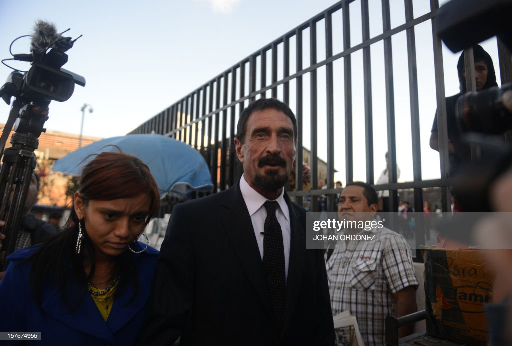 US antivirus software pioneer John McAfee walks with his girlfriend next to the Supreme Court in Guatemala City on December 04 2012 McAfee wanted for...