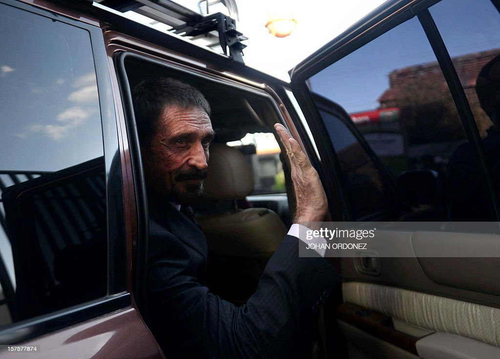 US anti-virus software pioneer John McAfee waves to journalists while leaving, in front of the Supreme Court in Guatemala City on December 04, 2012. McAfee, wanted for questioning over the murder of his neighbor last month in Belize, is seeking political asylum in Guatemala. AFP PHOTO / Johan ORDONEZ