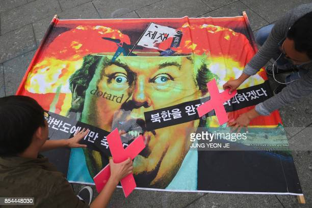 Antiwar activists attach 'X' signs on a banner showing a caricature of US President Donald Trump during an antiTrump rally near the US embassy in...
