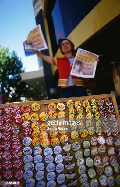 Anti-war badges for sale with Leftist newspaper seller in background.