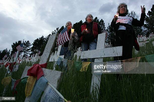 Antiwar demonstrators hold a candlelight vigil at a roadside cross memorial in honor of US troops that have been killed in Iraq March 19 2007 in...