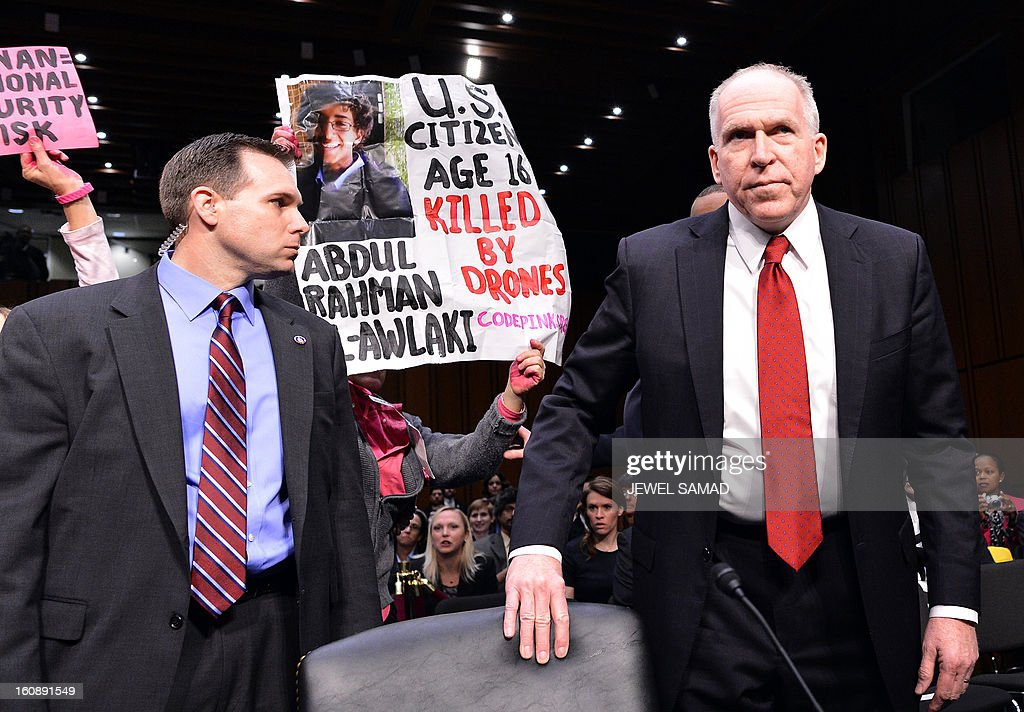 Anti-war protesters shout slogans as John Brennan (R), President Barack Obama's pick to lead the CIA, arrives to testify before a full committee hearing on his nomination to be director of the Central Intelligence Agency (CIA) in the Hart Senate Office Building in Washington, DC, on February 7, 2013. AFP PHOTO/Jewel Samad