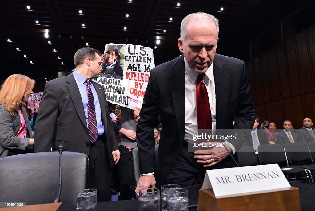 Anti-war protesters (back) shout slogans as John Brennan (R), US President Barack Obama's pick to lead the CIA, arrives to testify before a full committee hearing on his nomination to be director of the Central Intelligence Agency (CIA) in the Hart Senate Office Building in Washington, DC, on February 7, 2013. AFP PHOTO/Jewel Samad