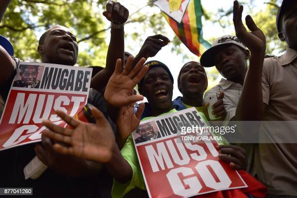 TOPSHOT AntiZimbabwe President hold placards during a gathering at Unity square on November 21 2017 in the capital Harare praying and asking for...