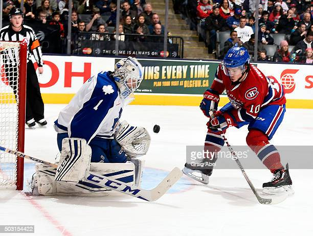 Antoine Bibeau of the Toronto Marlies and Charles Hudon of the St Johns IceCaps fight for a loose puck during AHL game action on December 26 2015 at...