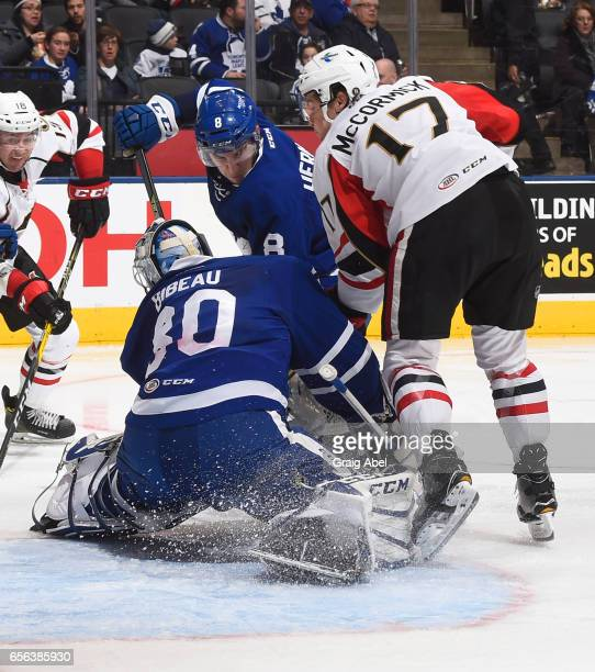 Antoine Bibeau of the Toronto Marlies controls the puck while Travis Dermott of the Marlies defends against Max McCormick of the Binghamton Senators...