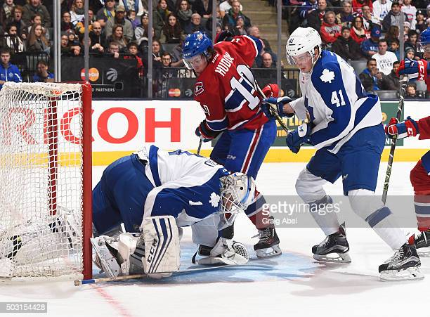 Antoine Bibeau of the Toronto Marlies covers the puck in front of Justin Holl of the Marlies and Charles Hudon of the St Johns IceCaps during AHL...