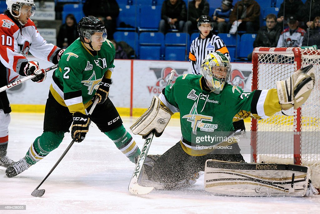 Antoine Bibeau #30 of the Val D'Or Foreurs makes a glove save on the puck during the QMJHL game against the Drummondville Voltigeurs at the Centre Marcel Dionne on February 14, 2014 in Drummondville, Quebec, Canada.