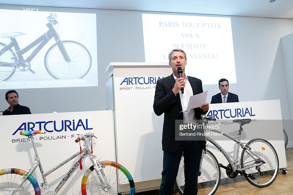 Antoine de Caunes who plays the auctioneer standing near bikes 'L'Atlas Bike' from L'Atlas (R) and 'Fly swing' by Louis Bottero (L) at 'Arty Bike' Auction to benefit Association des Tout P'tits at Artcurial on June 20, 2013 in Paris, France.
