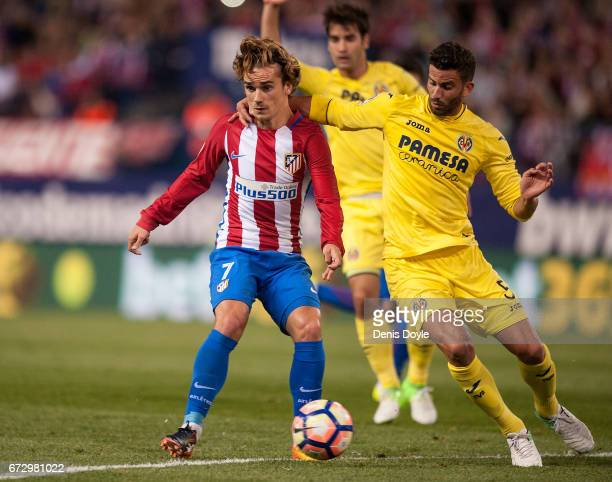 Antoine Greizmann of Club Atletico de Madrid is grabbed by Mateo Pablo Musacchio of Villarreal CF during the La Liga match between Club Atletico de...