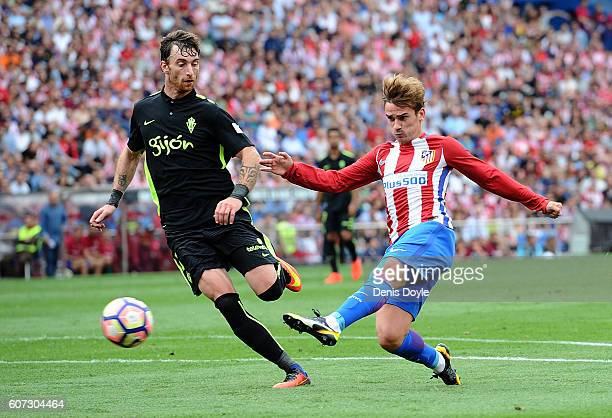 Antoine Greizmann of Club Atletico de Madrid shoots past Fernando Amorebieta of Sporting Gijon during the La Liga match between Club Atletico de...