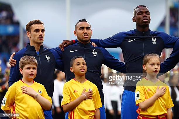 Antoine Griezmann Dimitri Payet and Paul Pogba of France line up for the national anthem prior to the UEFA Euro 2016 Group A match between France and...