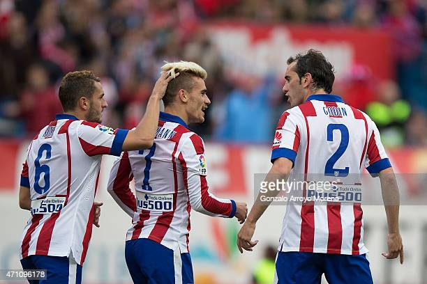 Antoine Griezmann of Atletico de Madrid celebrates scoring their second goal with team mate Koke and Diego Godin during the La Liga match between...