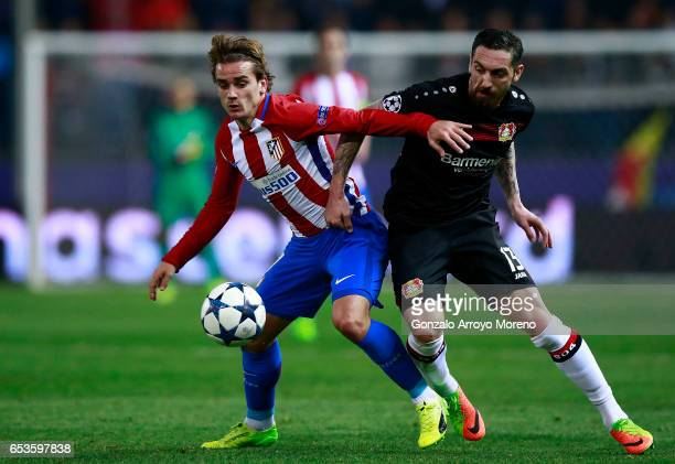 Antoine Griezmann of Atletico de Madrid competes for the ball with Roberto Hilbert of Bayer Leverkusen during the UEFA Champions League Round of 16...