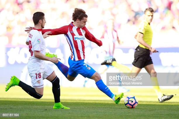 Antoine Griezmann of Atletico de Madrid competes for the ball with Sergio Escudero of Sevilla FC during the La Liga match between Club Atletico de...