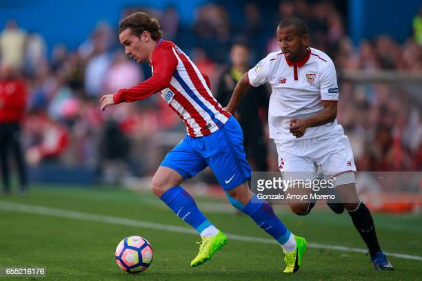 Antoine Griezmann of Atletico de Madrid competes for the ball with Mariano Ferreira of Sevilla FC during the La Liga match between Club Atletico de...