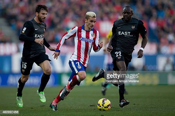 Antoine Griezmann of Atletico de Madrid runs for the ball against Nikolao Karampelas of Levante UD and his teammate Mohamed Sissoko during the La...