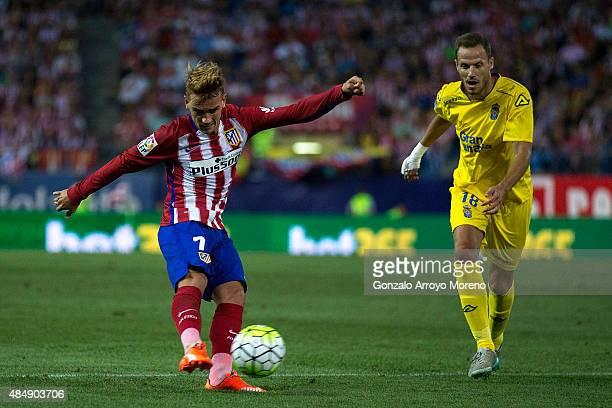 Antoine Griezmann of Atletico de Madrid strikes the ball ahead Javier Castellano of UD Las Palmas during the La Liga match between Club Atletico de...
