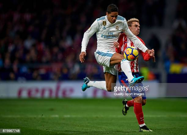 Antoine Griezmann of Atletico Madrid competes for the ball with Raphael Varane of Real Madrid during the La Liga match between Atletico Madrid and...