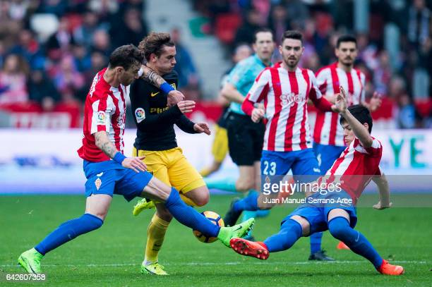 Antoine Griezmann of Atletico Madrid duels for the ball with Roberto Canella and Jorge Mere of Real Sporting de Gijon during the La Liga match...