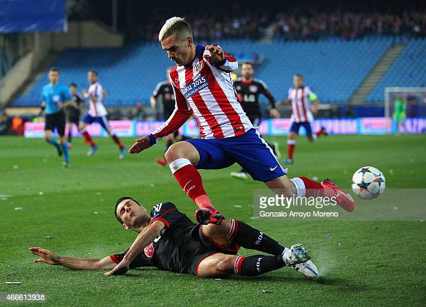 Antoine Griezmann of Atletico Madrid leaps over the challenge from Emir Spahic of Bayer Leverkusen during the UEFA Champions League round of 16 match...