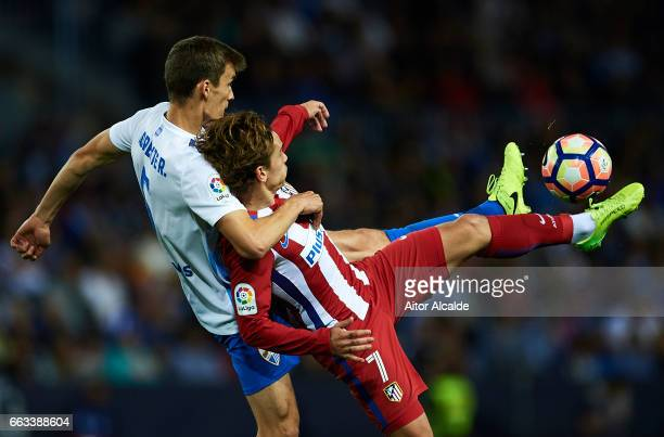 Antoine Griezmann of Club Atletico de Madrid competes for the ball with Diego Llorente of Malaga CF during La Liga match between Malaga CF and Club...