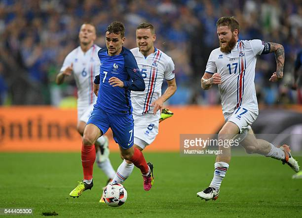 Antoine Griezmann of France and Aron Gunnarsson of Iceland compete for the ball during the UEFA EURO 2016 quarter final match between France and...
