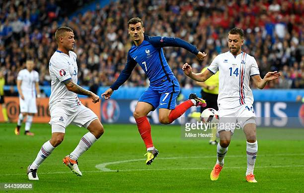 Antoine Griezmann of France competes for the ball against Ragnar Sigurdsson and Kari Arnason of Iceland during the UEFA EURO 2016 quarter final match...
