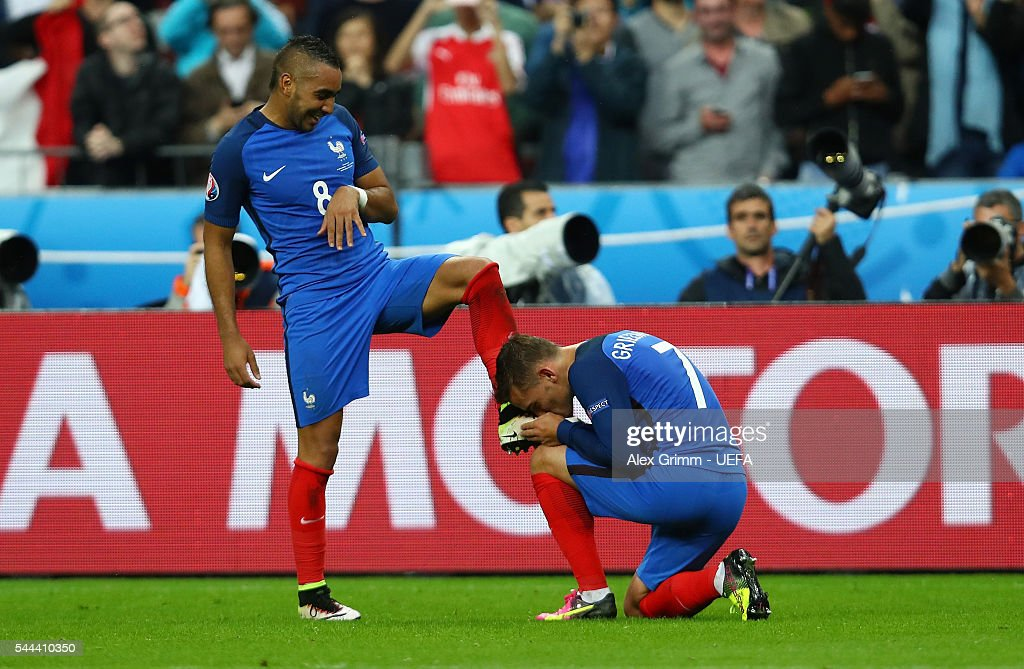 Antoine Griezmann of France kisses a boot of Dimitri Payet after their third goal during the UEFA EURO 2016 quarter final match between France and...