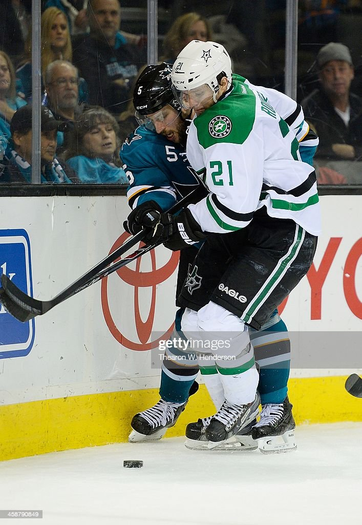Antoine Roussel #21 of the Dallas Stars collides with Jason Demers #5 of the San Jose Sharks during the third period at SAP Center on December 21, 2013 in San Jose, California. The Sharks won the game in an overtime shoot-out 3-2.
