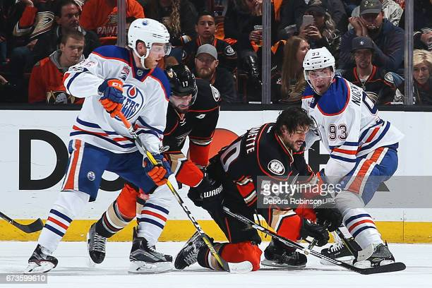 Antoine Vermette of the Anaheim Ducks battles against Ryan NugentHopkins and Drake Caggiula of the Edmonton Oilers after losing his helmet as Ryan...