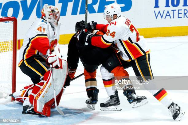 Antoine Vermette of the Anaheim Ducks battles in front of the net against Travis Hamonic and Mike Smith of the Calgary Flames during the game on...