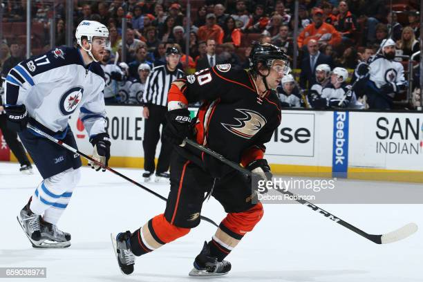 Antoine Vermette of the Anaheim Ducks skates against Adam Lowry of the Winnipeg Jets during the game on March 24 2017 at Honda Center in Anaheim...