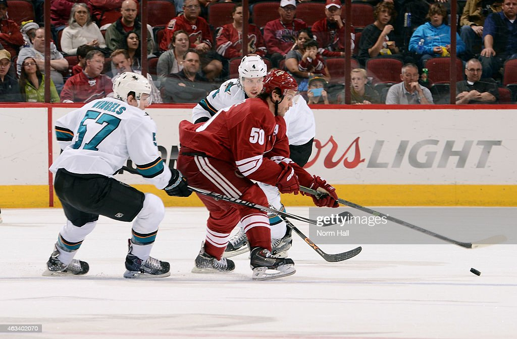 Antoine Vermette #50 of the Arizona Coyotes skates with the puck between Tommy Wingels #57 and Brenden Dillon #4 of the San Jose Sharks during the third period at Gila River Arena on February 13, 2015 in Glendale, Arizona.