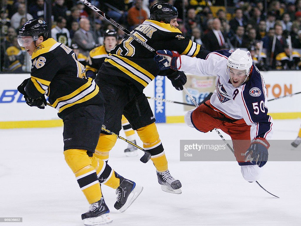 Antoine Vermette of the Columbus Blue Jackets falls to the ice after colliding with Johnny Boychuk and David Krejci of the Boston Bruins on January...