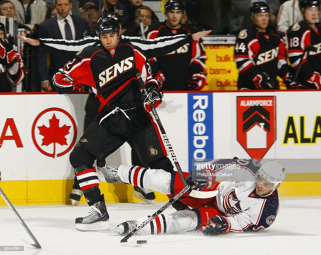 Antoine Vermette of the Columbus Blue Jackets gets knocked to the ice by Chris Kelly of the Ottawa Senators as he tries to carry the puck into the...