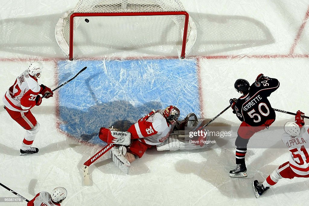 Antoine Vermette of the Columbus Blue Jackets scores on Jimmy Howard of the Detroit Red Wings as teammates Doug Janik and Valtteri Filppula watch the...