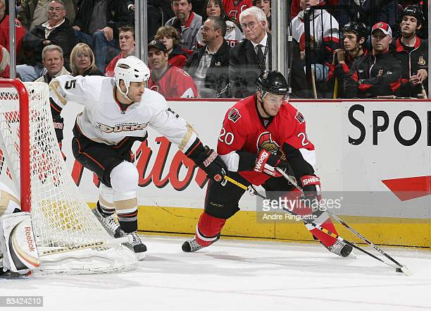 Antoine Vermette of the Ottawa Senators skates with the puck from behind the net as Steve Montador of the Anaheim Ducks pressures with a stick check...