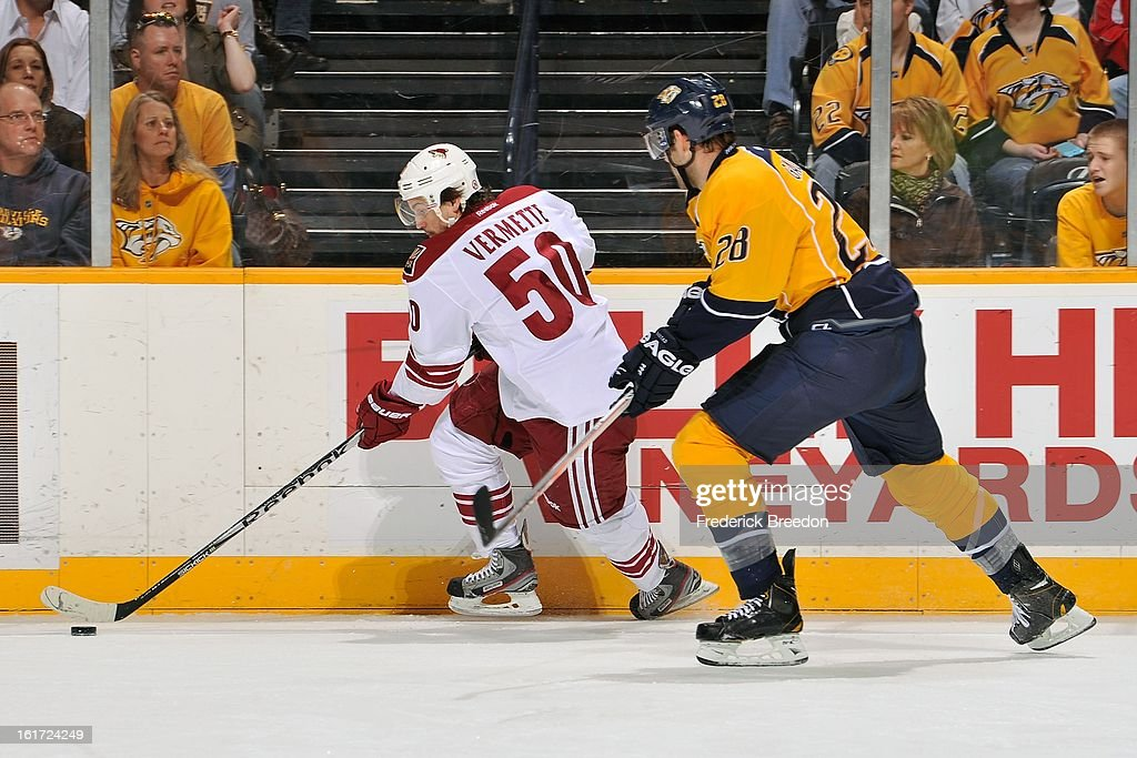 Antoine Vermette #50 of the Phoenix Coyotes carries the puck past Paul Gaustad #28 of the Nashville Predators at the Bridgestone Arena on February 14, 2013 in Nashville, Tennessee.