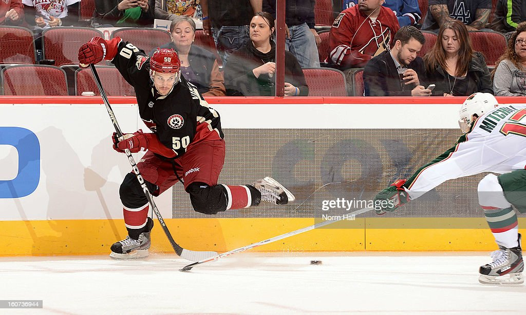 <a gi-track='captionPersonalityLinkClicked' href=/galleries/search?phrase=Antoine+Vermette&family=editorial&specificpeople=206302 ng-click='$event.stopPropagation()'>Antoine Vermette</a> #50 of the Phoenix Coyotes passes the puck back to the point around <a gi-track='captionPersonalityLinkClicked' href=/galleries/search?phrase=Torrey+Mitchell&family=editorial&specificpeople=4504539 ng-click='$event.stopPropagation()'>Torrey Mitchell</a> #17 of the Minnesota Wild during the second period at Jobing.com Arena on February 4, 2013 in Glendale, Arizona.