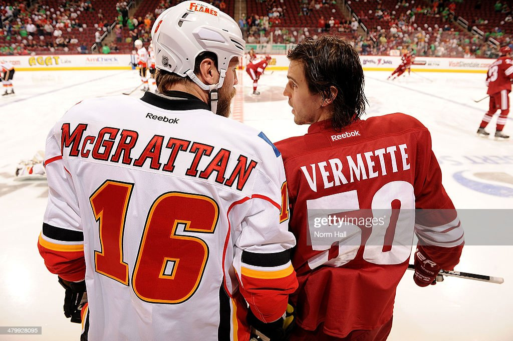 Antoine Vermette of the Phoenix Coyotes talks with Brian McGrattan of the Calgary Flames during pregame at Jobingcom Arena on March 15 2014 in...