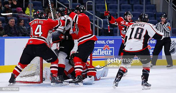 Antoine Waked of the RouynNoranda Huskies is pushed by Olivier Garneau and Aaron Dutra of the Quebec Remparts after a disallowed goal during their...