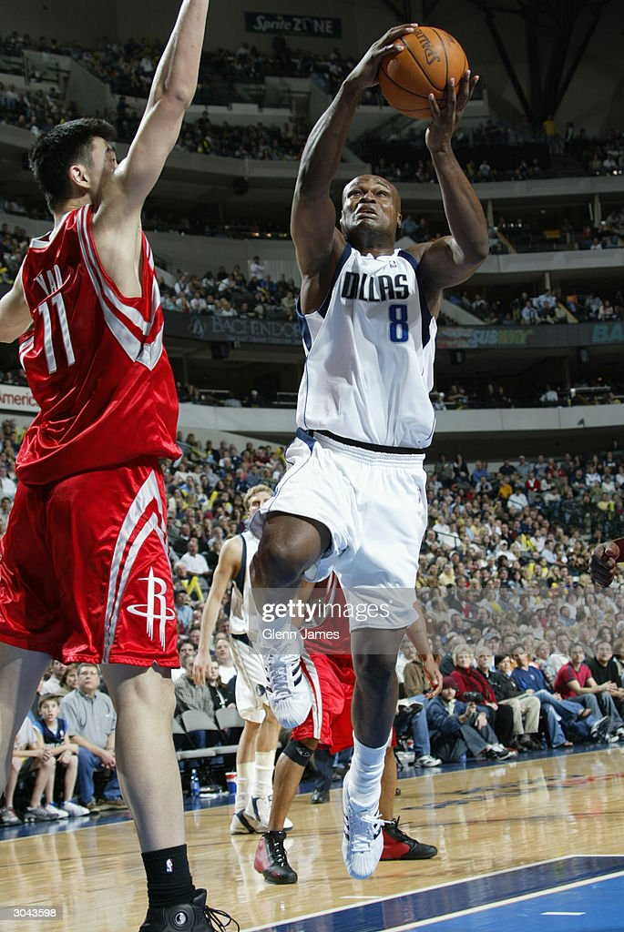 Antoine Walker #8 of the Dallas Mavericks goes up for a layup over Yao Ming #11 of the Houston Rockets during the game at the American Airlines Arena on February 21, 2004 in Dallas, Texas. The Mavericks won 97-88.